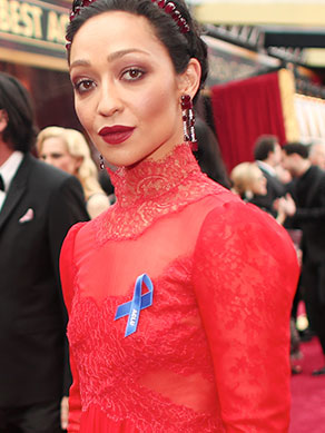 Ruth Negga walking the 2017 Oscars Red Carpet wearing an ACLU blue ribbon