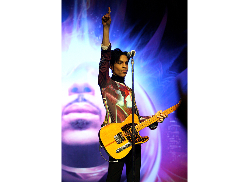 The legendary artist Prince performing on stage with his guitar