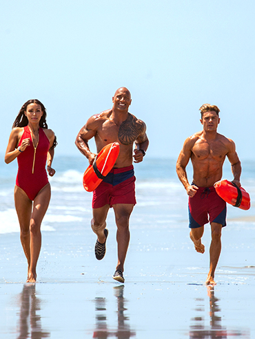 Baywatch Premier: Actors Ilfenesh Hadera, Dwayne Johnson and Zac Efron run along the surf in red bathing suits.