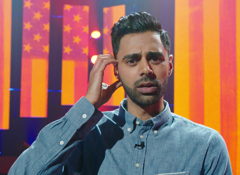 Hasan Minhaj on stage wearing a jean shirt with American flags projected on screens in the background