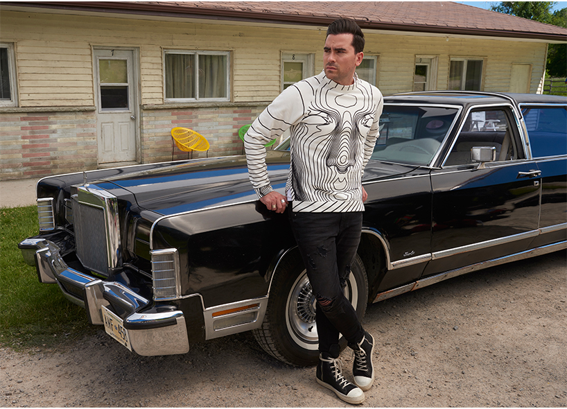 Dan Levy on Pansexuality: Dan Levy's character David leaning against a black car on the set of his TV show 'Schitt's Creek'; Inline image