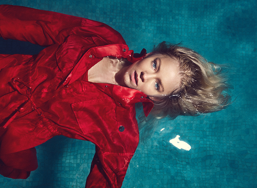 Astrid S, an up-and-coming pop star, floating in a blue pool while wearing a bright red coat