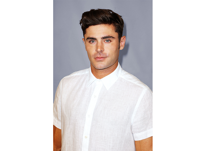 Zac Efron as Ted Bundy poses for press in Miami, Florida in a white shirt.