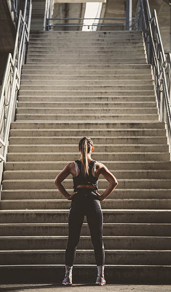 #Fitspo study: a woman in fitness gear stands at the base of a flight of steps, preparing to work out.