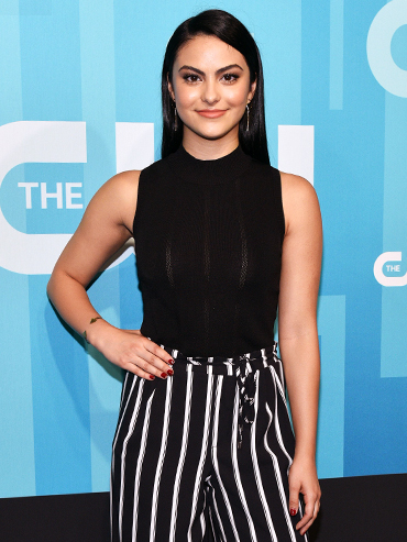 Actor Camila Mendes posing in a black top and striped pants