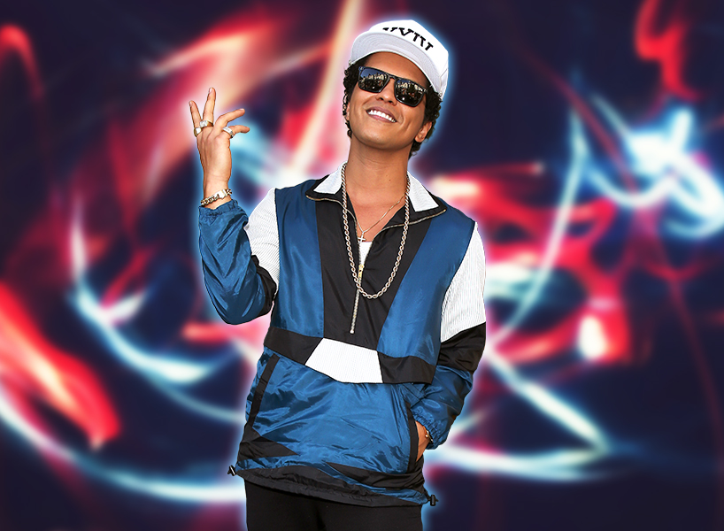Singer Bruno Mars posing in a white hat, black sunglasses and multicoloured jacket with his hand in the air
