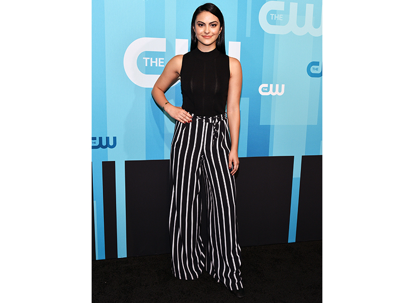Riverdale actor Camila Mendes posing in black top and striped pants
