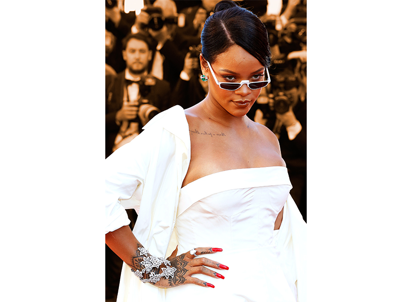 0b91e4407d7 Rihanna s Body Shaming Response  Rihanna wearing a white gown and   90s-inspired sunglasses