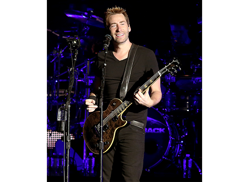 Nickelback frontman Chad Kroeger wearing all black and playing the guitar during a concert