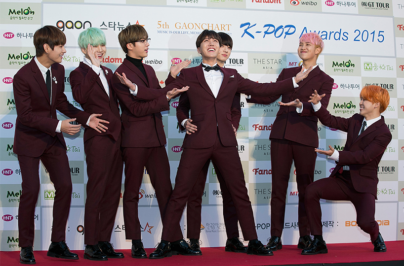 K-pop group BTS posing together in matching maroon suits at the K-Pop Awards in 2015