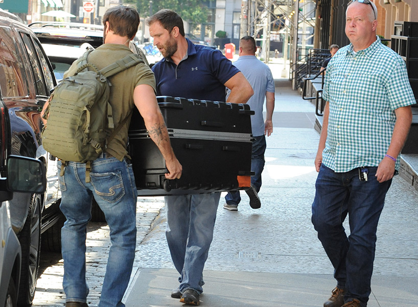 People think this photo of two bodyguards transporting a large black suitcase from the singer's Manhattan apartment is Taylor Swift in a box; inline