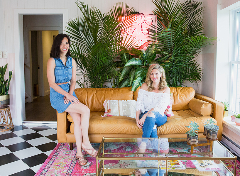 The June Motel owners Sarah Sklash and April Brown in the lobby of their motel, seated on a tan leather couch with green plants behind it