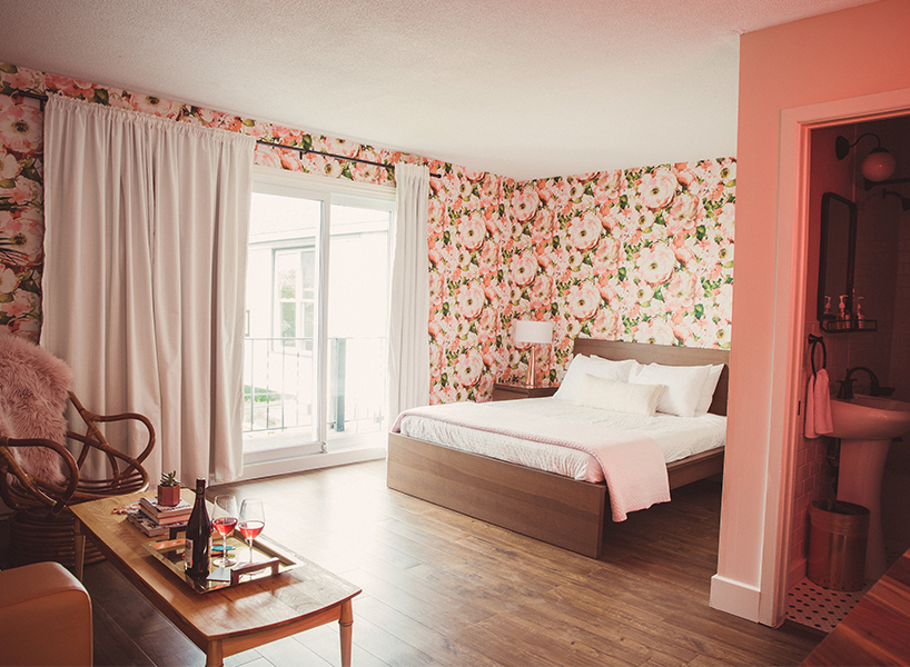 A motel room at The June with pink and green floral-patterned wallpaper, white curtains and white bedding