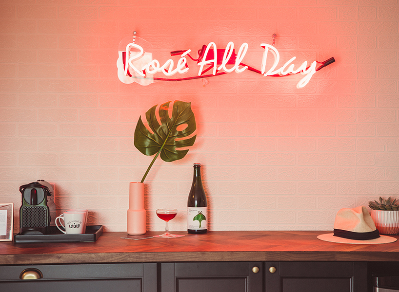 "A pink neon sign that reads ""rosé all day"""