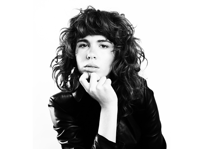 Grace Mitchell posing with curly hair in black and white