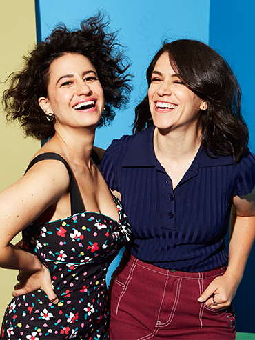 Broad City's Abbi and Ilana posing with smiles on a blue background