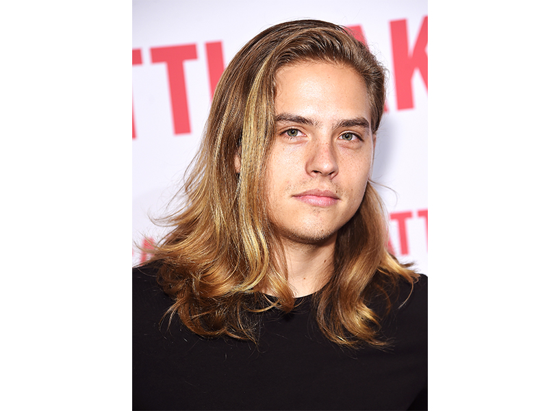 Actor Dylan Sprouse posing in a black t shirt