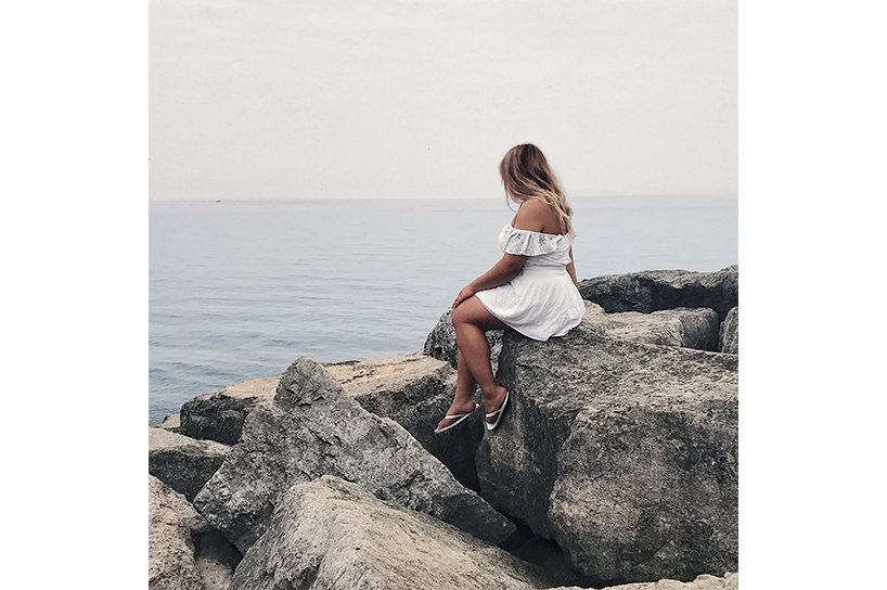 A photo of Janelle sitting on a rock and facing away from the camera wearing a frilly dress