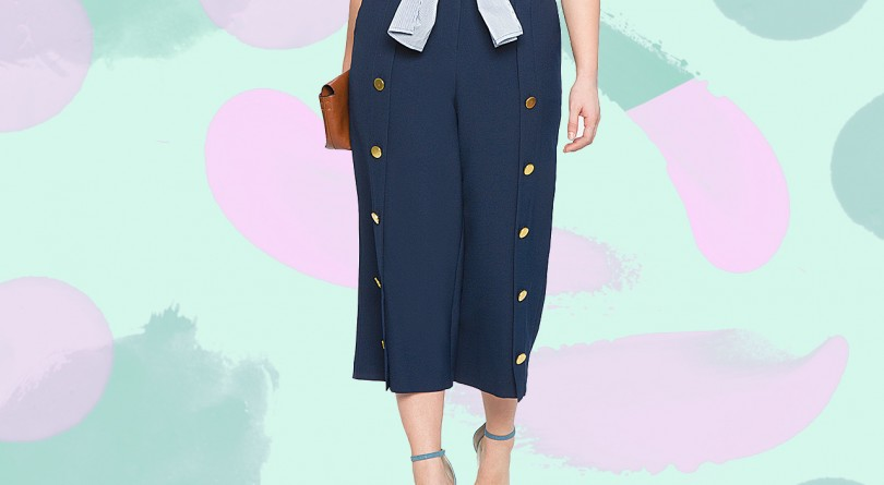 A woman wears wide-leg pants that are navy with gold buttons