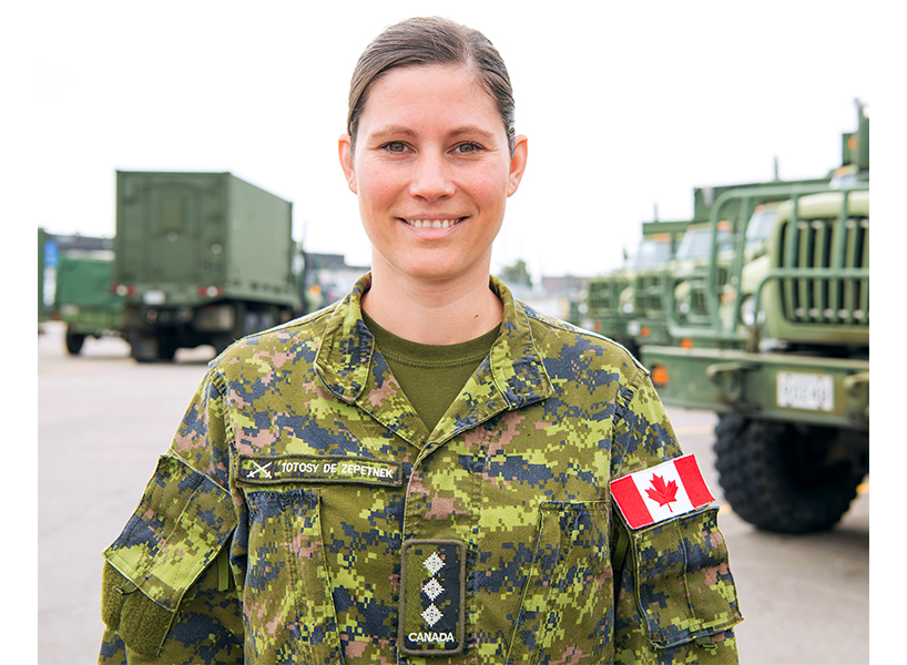 Chantal Totosy dressed in her army uniform with her brown hair in a low bun and a Canadian flag on her arm with army vehicles in the background