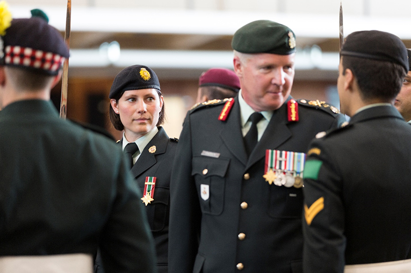 Chantal Chantal Totosy escorting Brigadier General Stephen Cadden, Commander of the 4th Canadian Division (The Army in Ontario) as he inspects the troops. She is in her formal uniform, and the photo is shot through a crowd and she is looking at the general as he inspects the troops