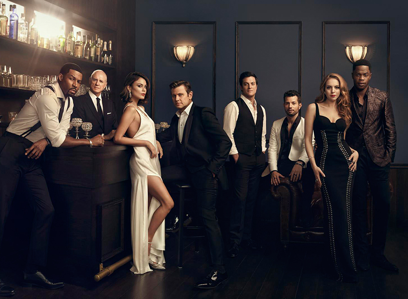 A dark and glitzy posed photo of the cast of Dynasty wearing formal attire, the women in long gowns and the men in suits and vests at a posh looking bar