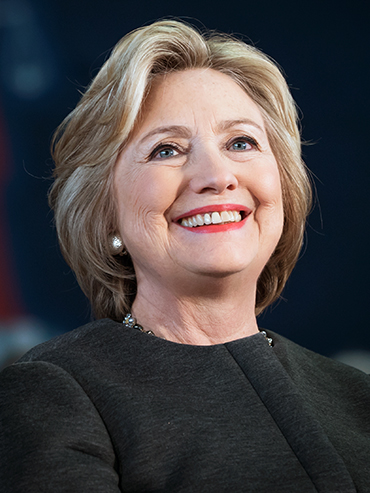 Hillary Clinton smiling in a dark coloured suit, coral lipstick and pearl earrings