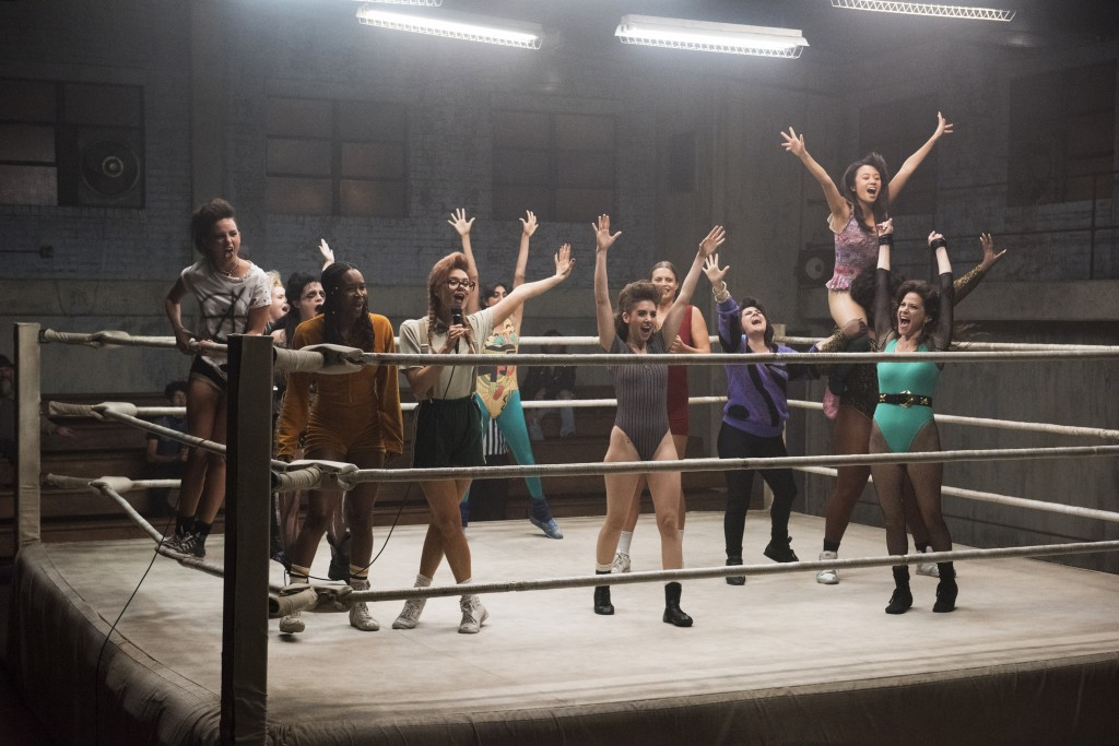 Ellen Wong TIFF Rising Star rides on the shoulders a cast mate in the wrestling ring in a still from Netflix's GLOW