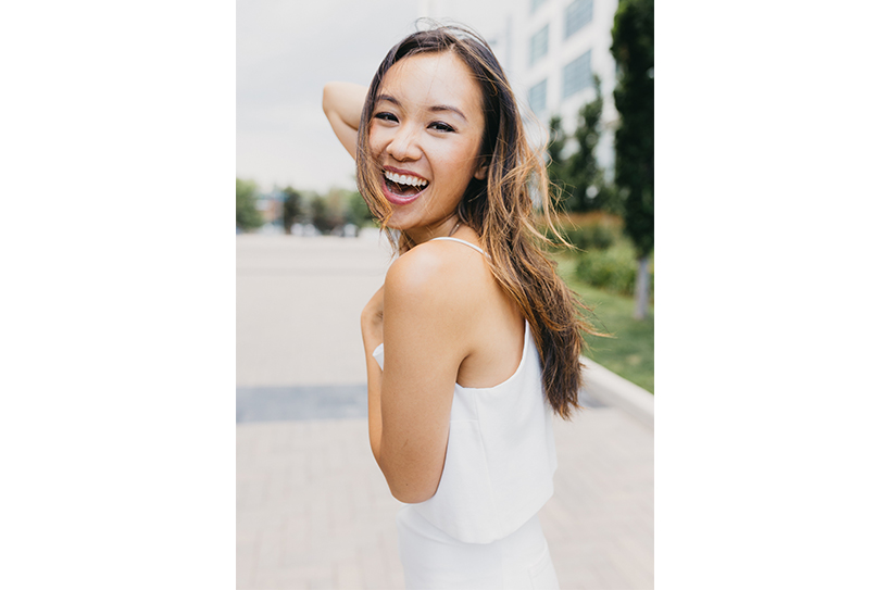 Ellen Wong looks over her shoulder and smiles, wearing a white dress