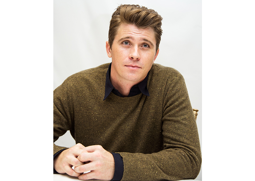 Garrett Hedlund posing in an olive green sweater
