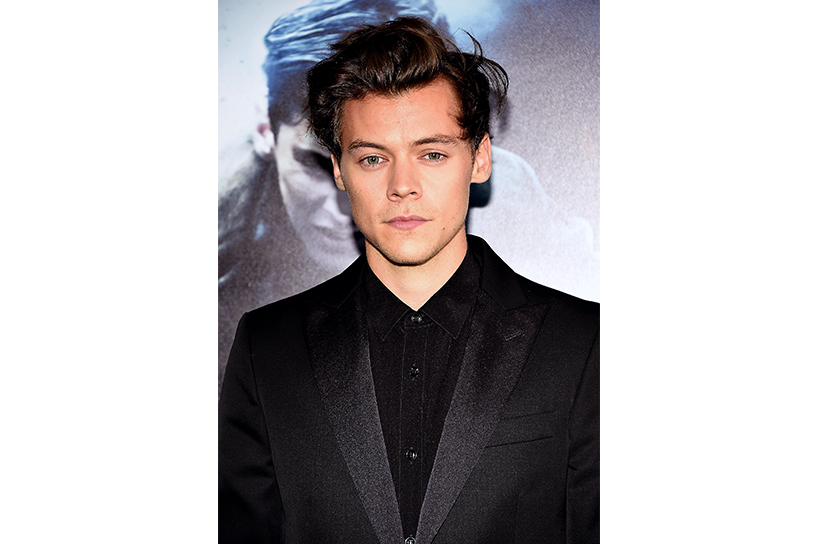 A photo of Harry Styles from One Direction. He is wearing a black shirt and suit