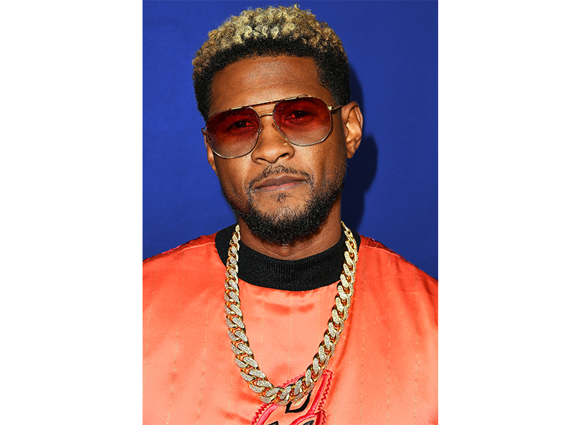 R&B star Usher posing in an orange shirt and gold chain