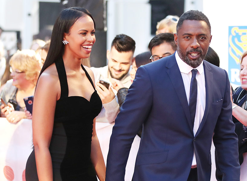 Idris Elba Girlfriend Sabrina Dhowre in a black dress with the actor in a navy blue suit on the TIFF 2017 red carpet; inline image.