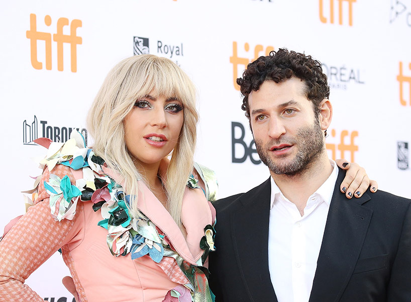 Lady Gage in a peach suit with director Chris Moukarbel in a white dress shirt and black suit jacket at the premiere of Gaga: Five Foot Two at TIFF.