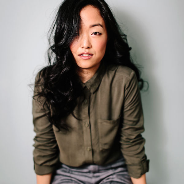 Andrea Bang poses in an olive silk blouse against a grey wall