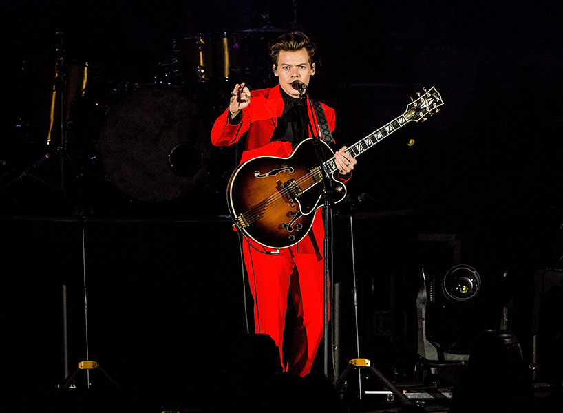 "HOLLYWOOD, CA - OCTOBER 21: Harry Styles performs during the CBS Radio Presents 5th Annual ""We Can Survive"" Show at the Hollywood Bowl on October 21, 2017 in Hollywood, California. Harry is wearing a red suit and a black shirt and pointing at the crowd holding a pic and wearing a guitar. (Photo by Timothy Norris/Getty Images)"