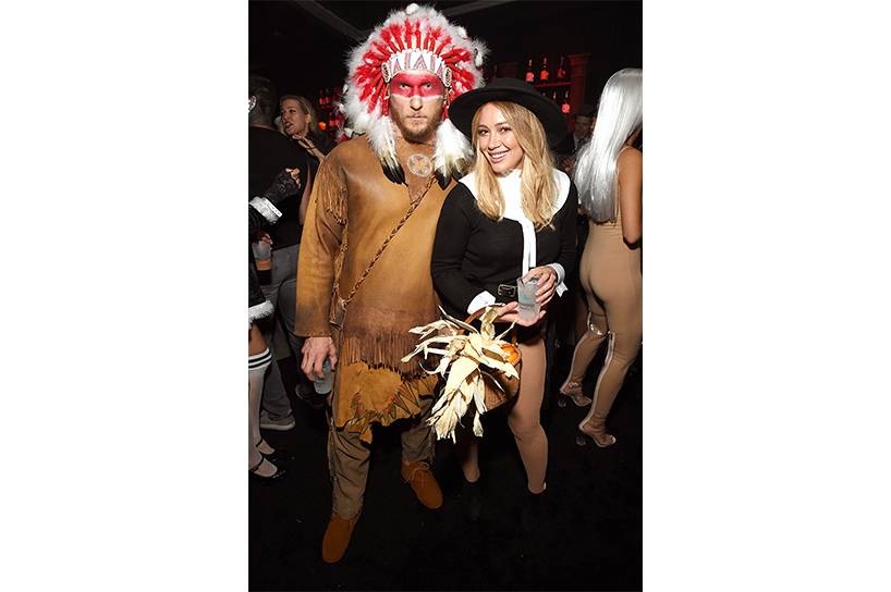 Offensive Halloween Costumes: Actress Hillary Duff and her date at a Halloween party. She is dressed up as a pilgrim and he is dressed as an Indigenous chief wearing a headdress and face paint