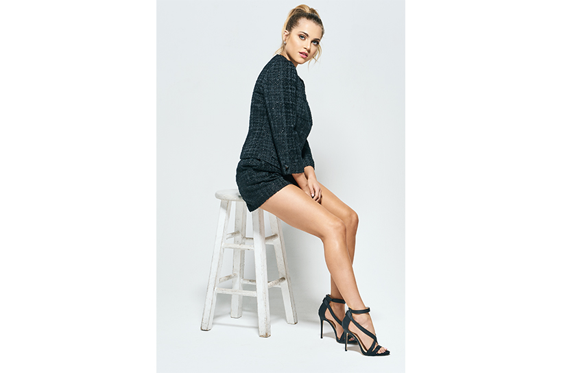 Actor Anne Winters of 13 Reasons Why Season 2 posing on a chair in a black dress