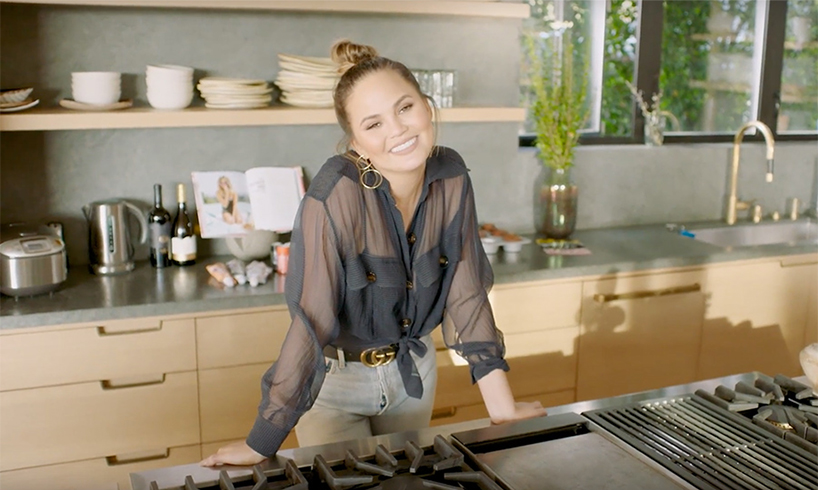 Chrissy Teigen smiling in her Beverly Hills kitchen