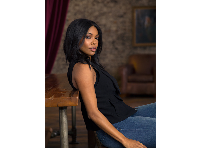 Actor Gabrielle Union posing in a black top and blue jeans