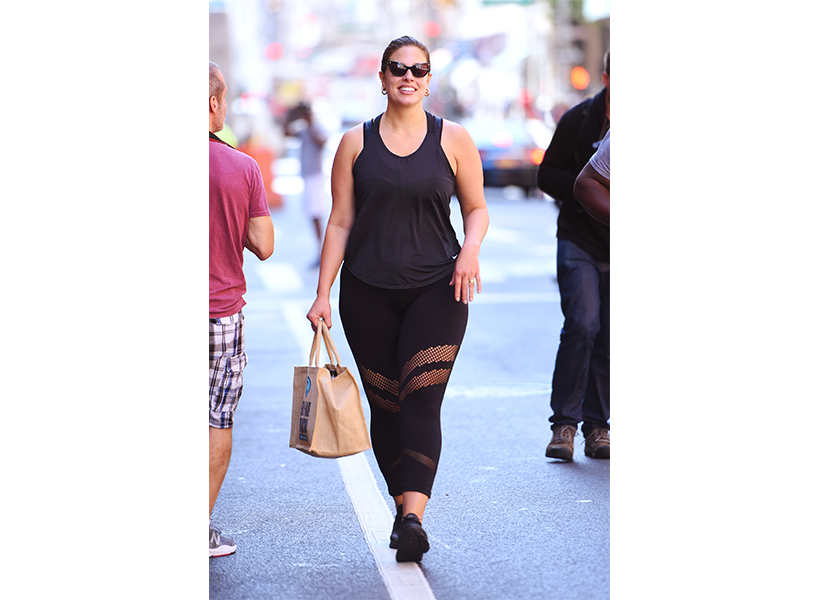 Model Ashley Graham carrying a brown tote bag, wearing a black exercise outfit