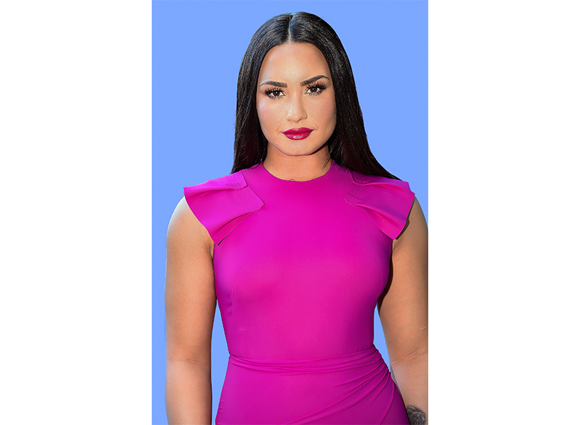 Demi Lovato with long, dark hair, wearing a bright pink dress