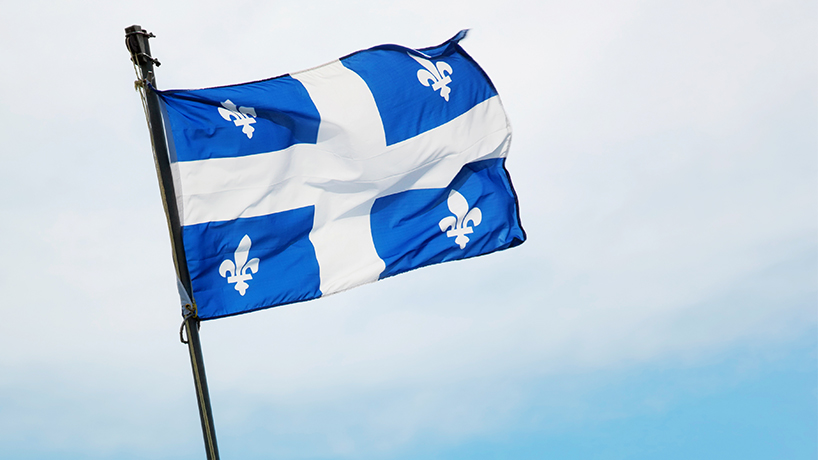 An image of the Quebec flag flapping in the sky