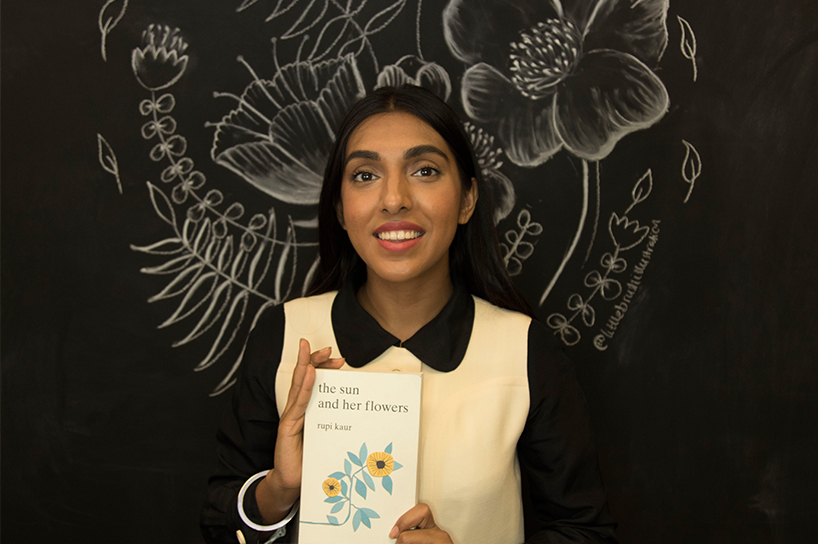"Poet Rupi Kaur in front of a chalkboard with flowers drawn on it, holding her book ""the sun and her flowers"""