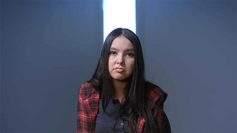 Shelly Chartier wearing a plaid shirt and her hair is down around her shoulders and a black button up on a dark background with a white column behind her head