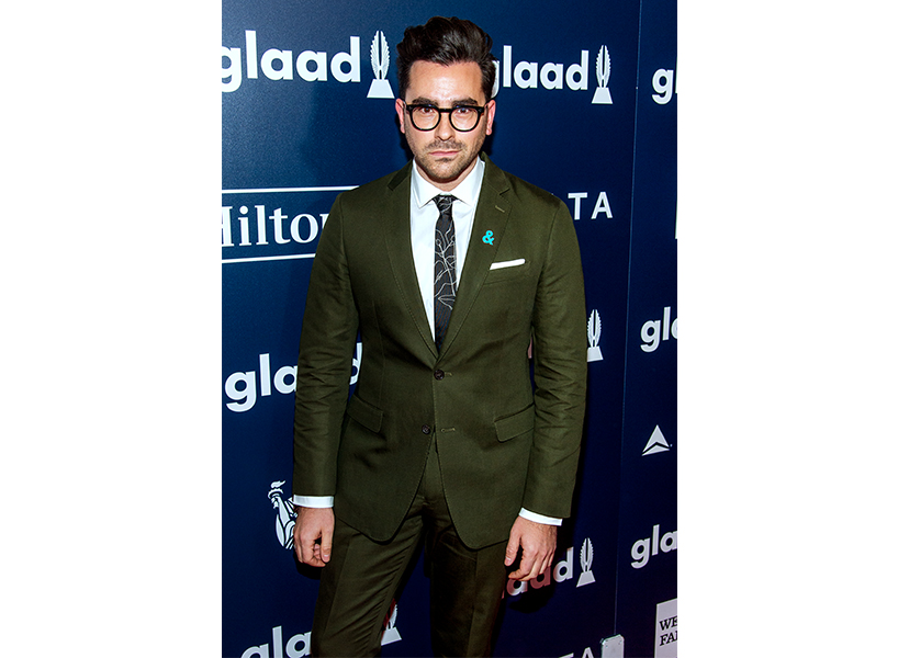 Dan Levy John Doyle: Dan Levy photographed on the carpet for an event in a green fitted suit and a black patterned tie, looking at the camera