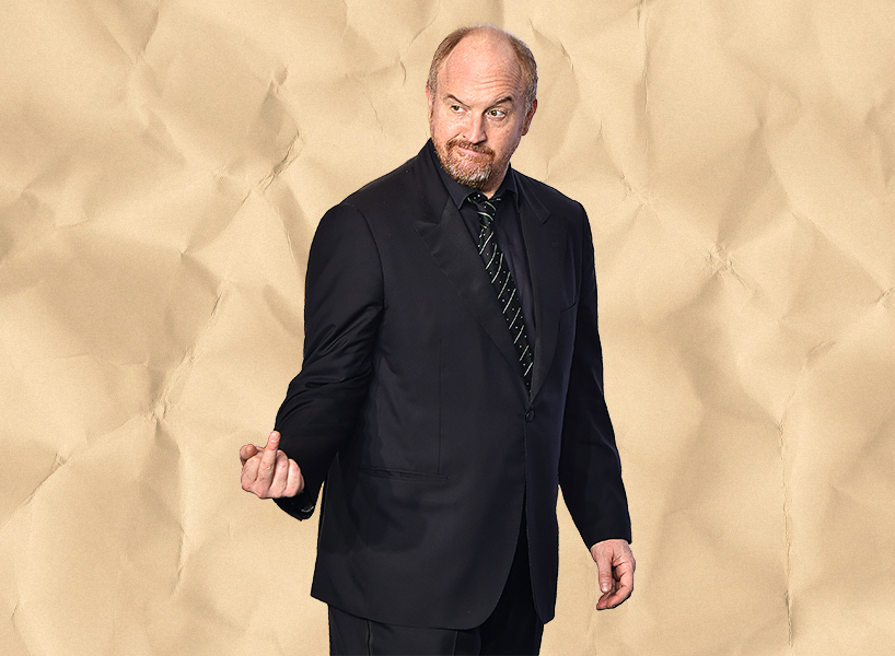 Comedian Louis C.K. in a black suit giving the middle finger