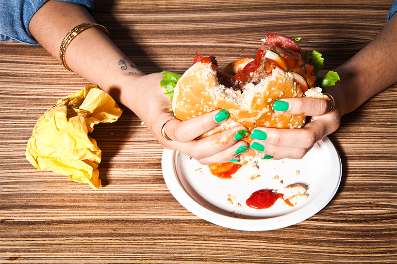 Clean eating: Two manicured hands hold onto a burger with a bit taken out of it