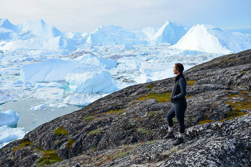 Jennifer Kilabuk looks out at water covered in chunks of ice while standing on a rocky mossy surface and wearing all black thermal wear
