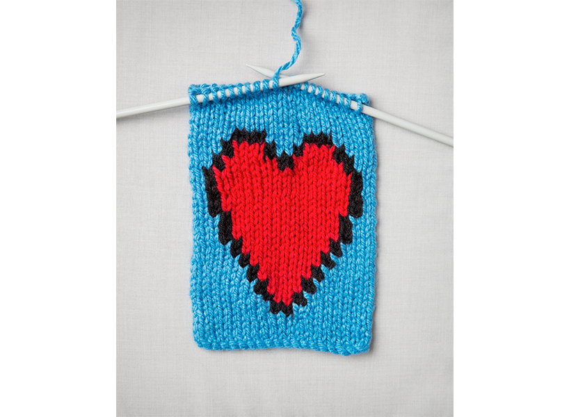 self-care: A pair of knitting needles knits a scarf with a heart in the middle